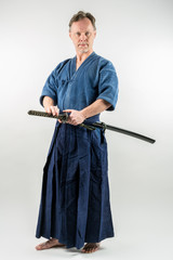 Adult caucasian male training Iaido about to draw a Japanese sword with focused look. Studio shot with white background.