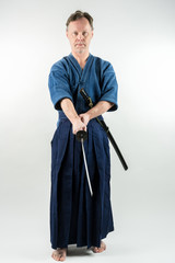 Adult caucasian male training Iaido holding a Japanese sword with focused look. Studio shot with white background.