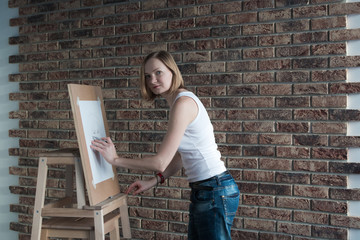 Female artist draws in the room