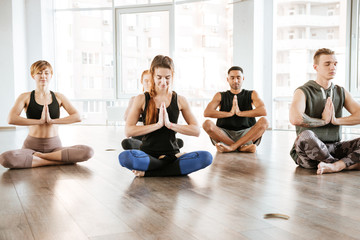 Group of people sitting and meditating at yoga studio