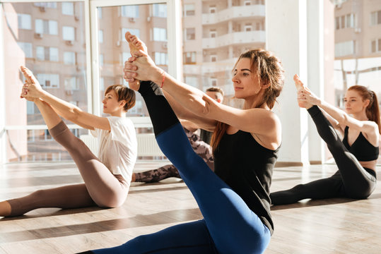 Group of people sitting and stretching legs in yoga studio