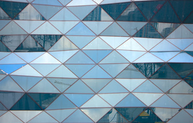 View of a modern glass skyscraper reflecting the blue sky,blue toned image