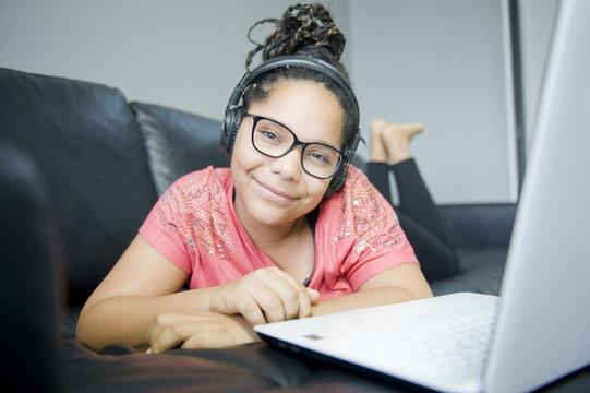 Jeune fille devant un ordinateur portable allongée sur un canapé