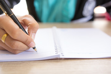 Women hand with pen writing on notebook.