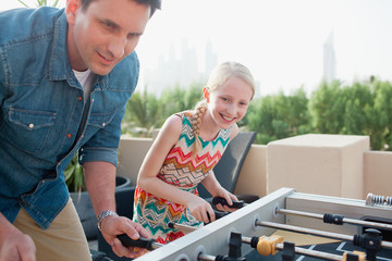 Father and daughter playing foosball.