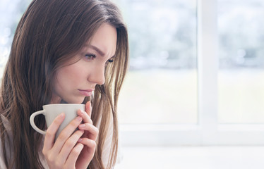 Young woman with cup of coffee or tea.