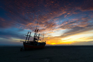 fishing boat on the beach with beautiful clouds in the morning