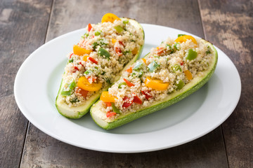 Stuffed zucchini with quinoa and vegetables on wooden background