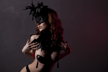 Sexy slim woman, burlesque dancer, unrecognizable stripper in black mask and feathers. Dark background with red lightening