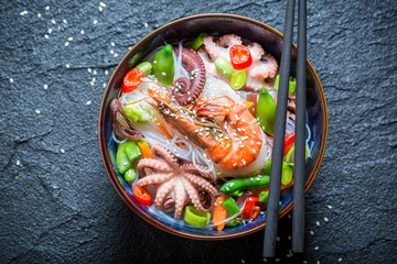 Hot seafood noodle in dark bowl with chopsticks