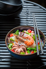 Enjoy your seafood noodle in dark bowl with chopsticks