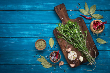 Herbs and spices at blue wooden table.