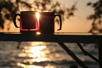 Couple thermos cup with sunset