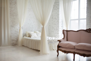 Bedroom in soft light colors. Big comfortable elegant double bed in white brick loft interior with large window