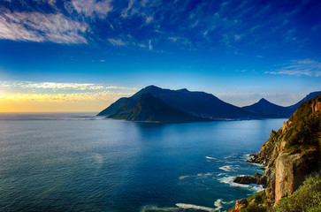 South Africa Hout Bay Cape Town blue hour scenic, peaceful and romantic panoramic landscape and seascape with a golden sunset over a blue quiet sea with mountains and a blue sky with clouds
