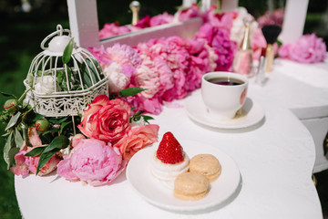 beautiful pink flowers and cup of coffee standing on a white tab