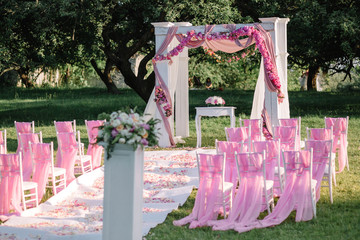 arch for the wedding ceremony and pink chairs standing outdoors