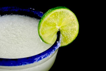 Blue rimmed glass with margarita and lime slice against a black background