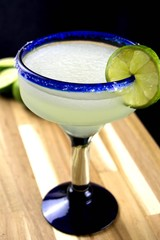 Margarita with lime slice in a blue rimmed glass on a wood surface