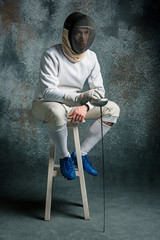 The man wearing fencing suit with sword against gray