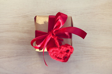 surprise for favorite person/ gift with a red bow and a heart symbol on a light wooden table top view