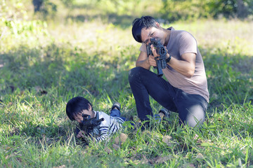 joyful happy Father and son with playing gun in the forest..