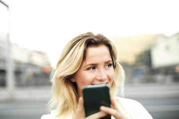 Happy young woman using mobile phone in city against clear sky