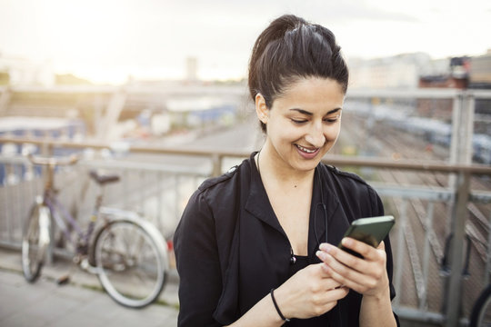 Happy young woman using a smart phone in city