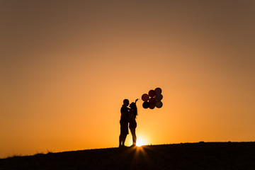 silhouette of a couple playing with balloons at sunset