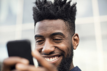 Low angle view of happy man using smart phone