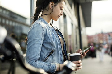 Side view of woman holding smart phone and coffee cup in city