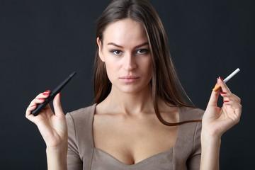 Junge schöne Frau mit E-Zigarette und normaler Zigarette