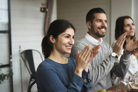 Smiling business professionals clapping while sitting at table during winetasting