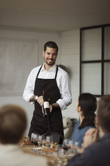 Happy man showing wine bottle to business people at table