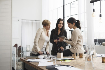 Happy businesswomen looking at digital tablet while standing in office