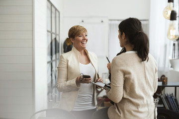 Happy businesswomen talking while standing in office