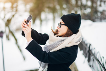 Portrait beautiful girl in black hat and coat with scarf make selfie