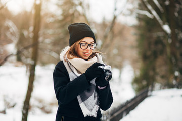 Cheerful girl photographer in black glasses in a black hat and coat and gloves with scarf in the winter park makes photo on old retro film camera