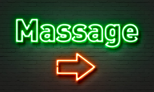 Massage neon sign on brick wall background.