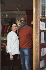 Portrait of smiling owners standing at store entrance