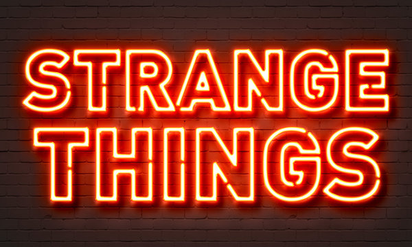 Strange things neon sign on brick wall background.