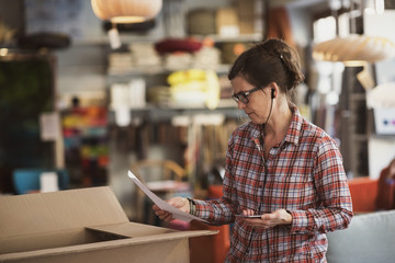 Owner reading document while listening music at store