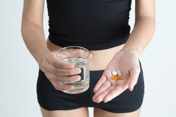 Woman hand holding pills and medicine tablets with glass of water on white background