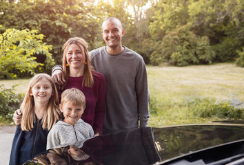 Portrait of happy family standing by black electric car at park