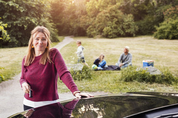 Portrait of happy woman standing by electric car with family in background at park