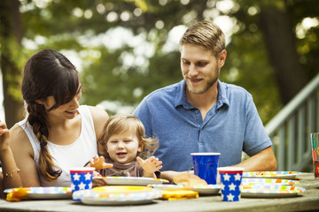 Parents eating meal with their son outdoors