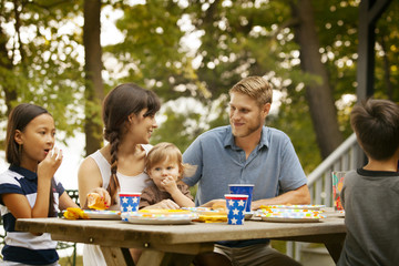 Family with kids (6-7,8-9, 12-17 months) eating lunch at picnic table