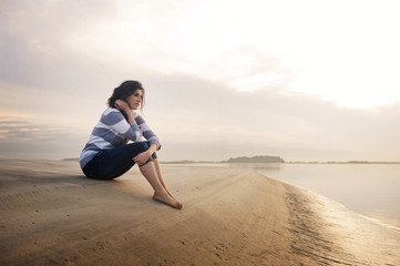 Young woman sitting on sandbar at sunset