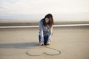 Woman drawing heart in sand on beach