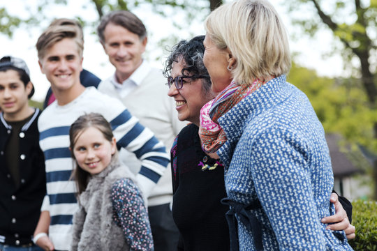 Smiling mature woman with family and friends at yard